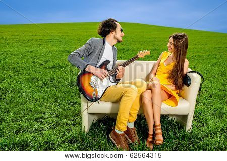 Man Playing Lovely Song To The Girl That Like It On The Couch On The Green Field