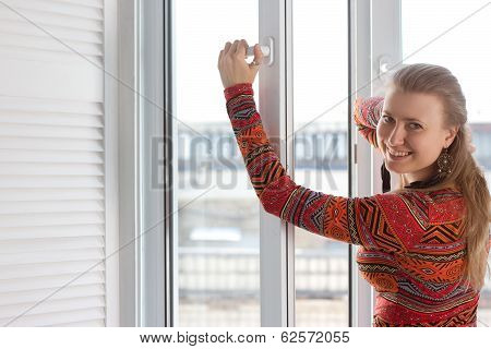 Woman opens a plastic window