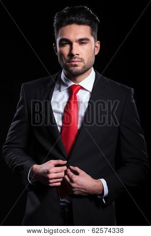 young business man looking into the camera and unbuttoning his suit jacket. on a black background
