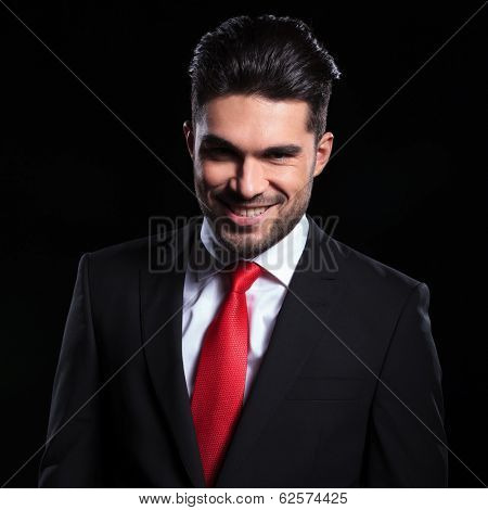 young business man looking into the camera with an evil smile on his face. on a black background