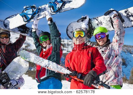 Four friends holding snowboards and skies