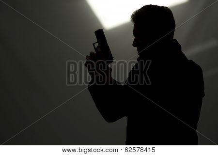 one man killer policeman aiming gun silhouette studio grey background