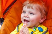 Funny Toddler Boy Smiling Outdoor In Orange Stroller