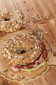 stock photo of bagel  - Whole grain bagel with bacon on wooden background - JPG