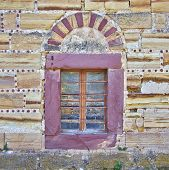 arched window on red and ocher colored stone wall