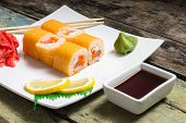 image of chopsticks  - Traditional Philadelphia sushi rolls on white plate with chopstick and wasabi - JPG
