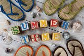 Childrens Blocks Spelling Out Summer Time on a rustic wooden boardwalk. The words are surrounded buy