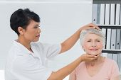pic of chiropractor  - Female chiropractor doing neck adjustment in the medical office - JPG