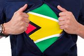 Young Sport Fan Opening His Shirt And Showing The Flag His Country Guyana, Guyanese Flag