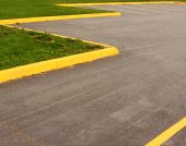stock photo of parking lot  - An empty paved parking lot with yellow lines and curbs borders a grass landscape - JPG