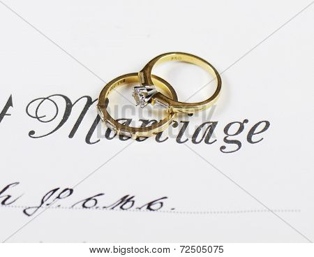Wedding And Diamond Engagement Rings On Marriage Certificate Closeup Macro