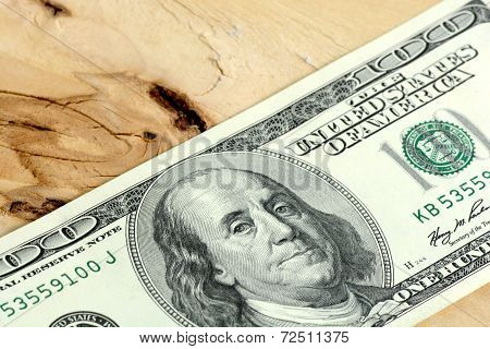 One Hundred Dollars Banknotes On Wooden Background