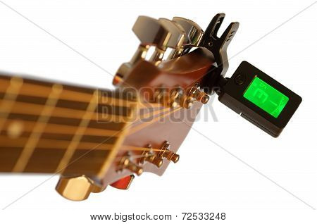 Detail of acoustic guitar with guitar clip tuner