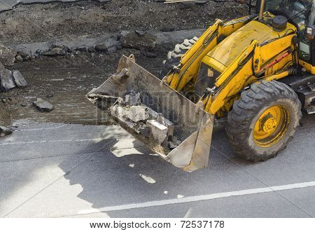 Bulldozer carries  in the bucket ruined asphalt.