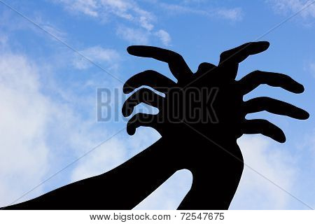 Spider Shape Hand Silhouette In Blue Sky And Cloud.