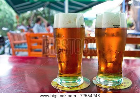 Two beers  in garden pub on table.