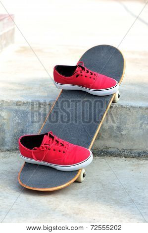 skateboard and red sneakers at outdoor skatepark