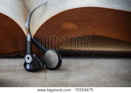 Earphones Hung On An Opened Book