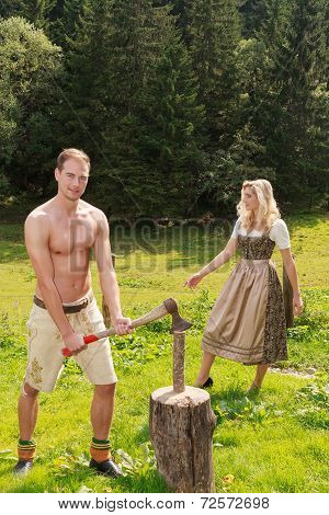 Young Bavarian man with leather trousers chopping wood on a summer pasture