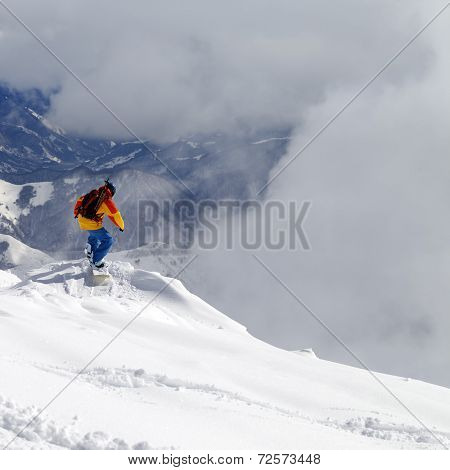 Snowboarder On Off-piste Slope An Mountains In Mist