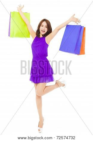 Happy Young Woman Walking And Holding Shopping Bags