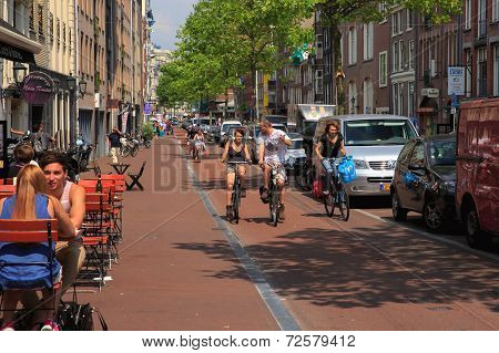 Ca Typical Amsterdam Street With Cyclists And Cafes, Holland, Netherlands.
