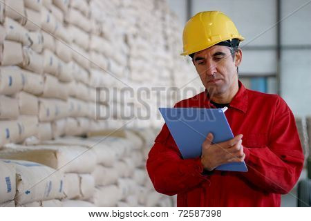 Worker Writing On Clipborad In Warehouse