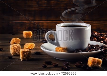 Cup of coffee in the old rustic style with cane sugar cubes and coffee beans.