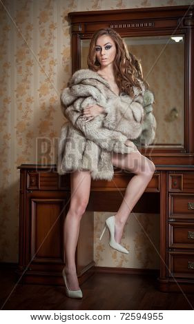 Attractive sexy young woman wearing only a fur coat posing provocatively indoor. Sensual redhead