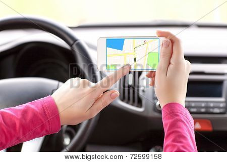 Female Driver Hand Holding A Phone With Interface Navigator On A Screen