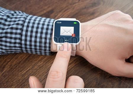 Male Hands With White Smartwatch With Email On The Screen Over A Wooden Table