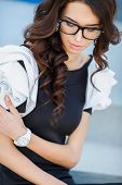 picture of wrist  - young business woman checks time on her wrist watch standing on street against modern office building - JPG