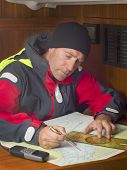 image of longitude  - Sailor studying navigation chart of coastal area - JPG