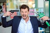 stock photo of petrol  - Emotional businessman shooting himself over crazy petrol prices - JPG