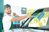 picture of petrol  - Washing car window while filling petrol cars at gas station - JPG