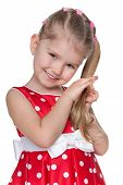 stock photo of shy girl  - A portrait of a shy little girl in a red polka dot dress on the white background - JPG