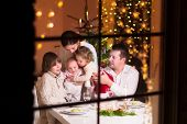 picture of christmas dinner  - Young big family celebrating Christmas enjoying dinner view from outside through a window into a decorated living room with tree and candle lights happy parents eating with three kids - JPG