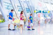 pic of big-girls  - Big happy family with three kids traveling by airplane at  airport parents with teenager boy toddler girl and little baby holding colorful luggage for summer beach vacation  - JPG