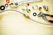 stock photo of plumbing  - tools plumbing on a light woody background - JPG