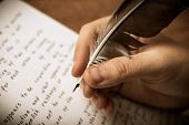 stock photo of fountains  - writer writes a fountain pen on paper work close up - JPG