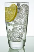 stock photo of glass water  - Sparkling drink in glass with ice cubes and lemon slice - JPG