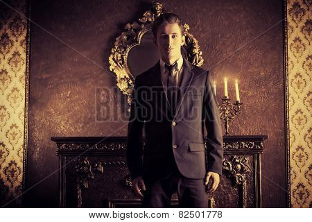 Handsome respectable man in elegant suit stands in a room with classic vintage style. Business. Fashion.