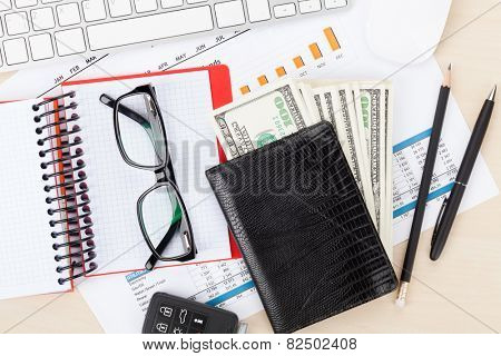 Office desk with reports, blank notepad and money cash. View from above