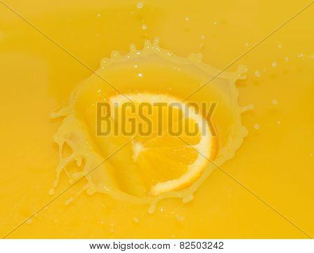 Ripe Juicy Orange Slice Falling into Juice
