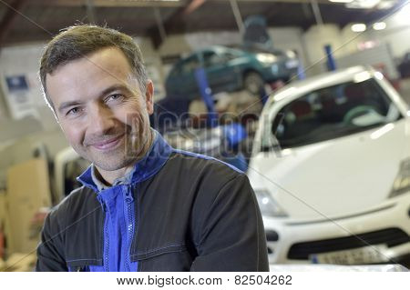 Portrait of smiling mechanic in auto repair shop
