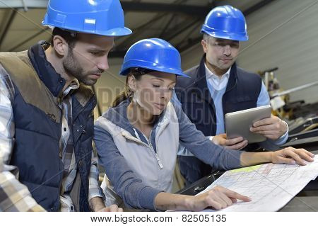 Industrial engineers meeting in mechanical factory