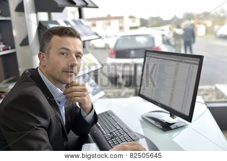 Car dealer sitting in front of desktop computer