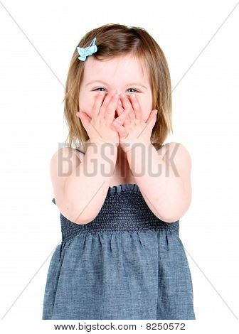 Cute little girl holding her hands over her mouth