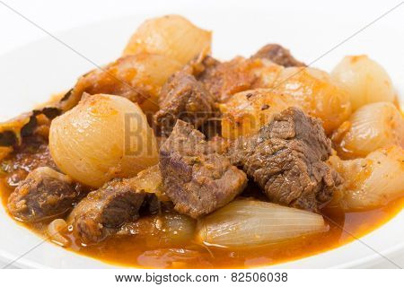 A bowl of traditional Greek stifado, a beef, onion and tomato stew, with garlic, herbes and seasoning