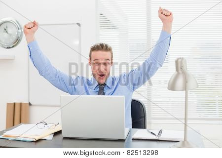 Excited businessman with arms up cheering in his office